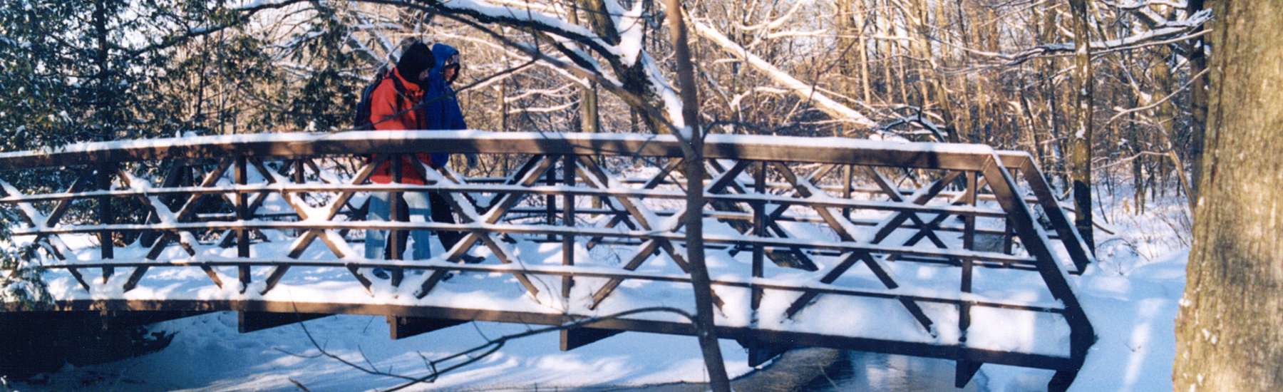 Two people cross a snowy bridge on foot in Waterloo Park